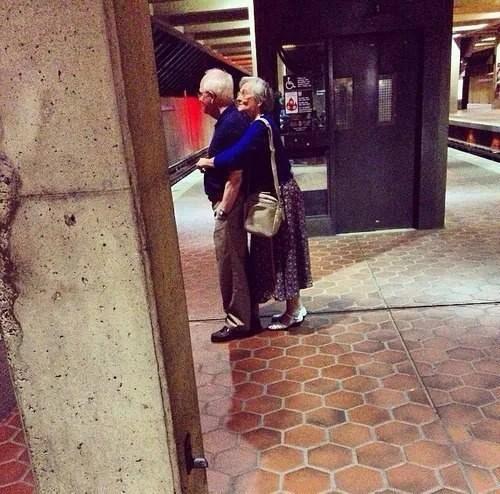 coppia anziana si abbraccia in metro