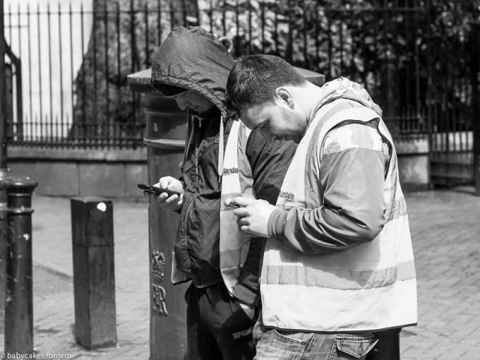 persone camminano guardando telefono