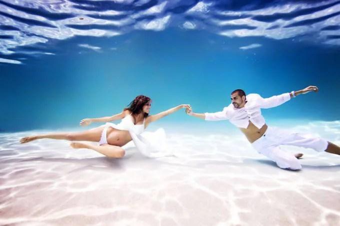 donna e uomo sott acqua vestiti bianco