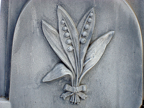 Detail of a lily of the valley from a well-preserved zinc monument, showing the characteristic blue-grey patina. The lily symbolizes purity and resurrection, since it is one of the first flowers to bloom in the spring. Image by Svadilfari.