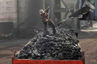 A labourer loads coal onto a truck at Sanyuan Coal Mine in Changzhi, Shanxi province, China