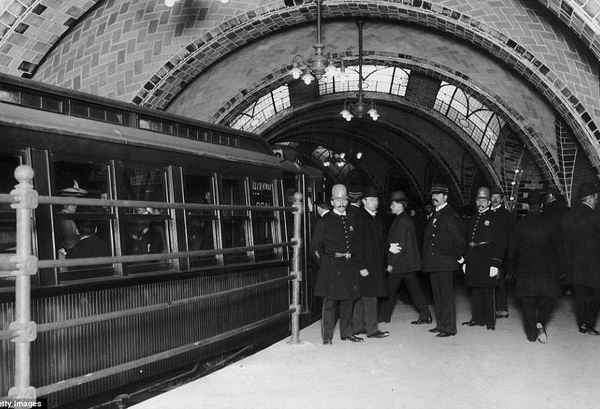NYPD officers and conductor with commuters on City Hall platform