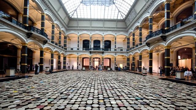 """Besucher betrachten am 02.04.2014 im Martin-Gropius-Bau in Berlin im Lichthof die Installation """"Stools"""" (Hocker) des Konzeptkünstlers Ai Weiwei. Die 6000 antiken hölzernen Schemel sollen symbolisieren, wie die Chinesen bei der Landflucht ihre Vergangenheit zurücklassen. Die Ausstellung Evidence von Ai Weiwei dauert vom 03.04.2014 bis zum 07. Juli 2014. Foto: Kay Nietfeld/dpa +++(c) dpa - Bildfunk+++"""