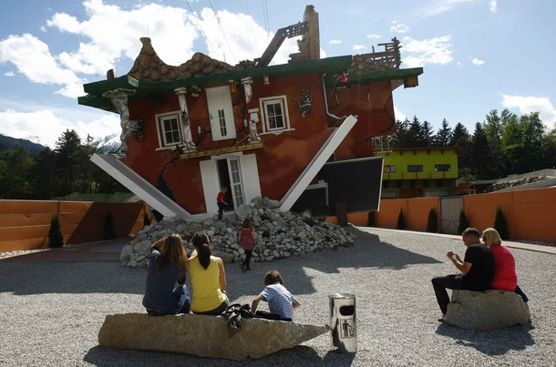 People sit in front of a house, which was built upside down by Polish architects Irek Glowacki and Marek Rozhanski, in the western Austrian village of Terfens May 5, 2012. The project is meant to serve as a new tourist attraction in the area, and is now open for public viewing. Picture taken May 5, 2012. REUTERS/Dominic Ebenbichler