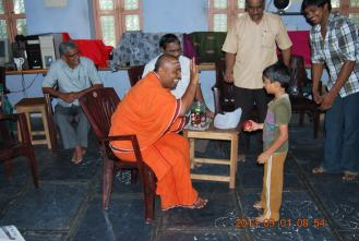Rev. Swami Paramasukhanandaji Maharaj interacting with a kid