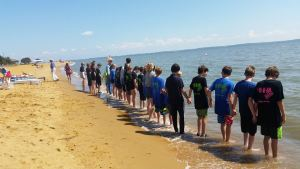 "8th Grade STEM students from Old Mill Middle School South STEM program wade into the Bay to test the water's clarity led by Former State Senator Bernie Fowler of Calvert County to conduct a ""Sneaker Index"" to assess water quality."