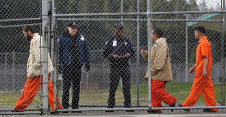 Inmates walk past correctional officers at the Washington Corrections Center in Shelton, Wash. (AP Photo/Elaine Thompson)