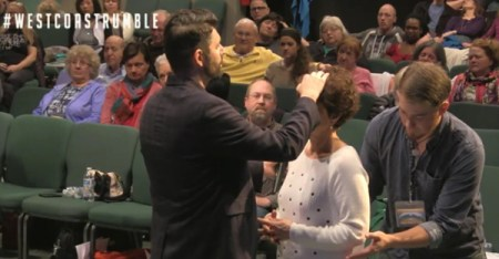 """Charlie Shamp prays over a woman March 3 at the Seattle Revival Center. The man in back of her is known as a """"catcher"""" in case she falls to the ground. (Photo courtesy of Julia Duin)"""