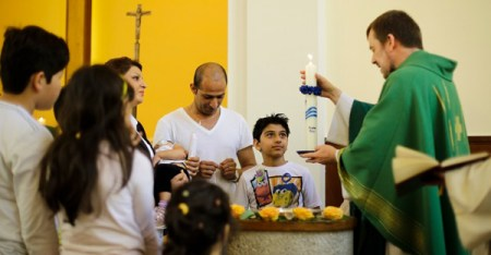 Pastor Gottfried Martens lights a candle during a service to baptize people from Iran, in the Trinity Church in Berlin, Aug. 30, 2015. (Markus Schreiber / AP)