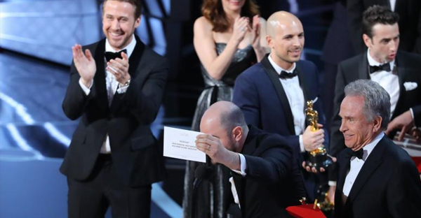 89th Academy Awards - Oscars Awards Show - Producer Jordon Horowitz holds up the card for the Best Picture winner Moonlight. At left is Ryan Gosling and right is presenter Warren Beatty who mistakenly announced La La Land as the best picture winner. (REUTERS/Lucy Nicholson)