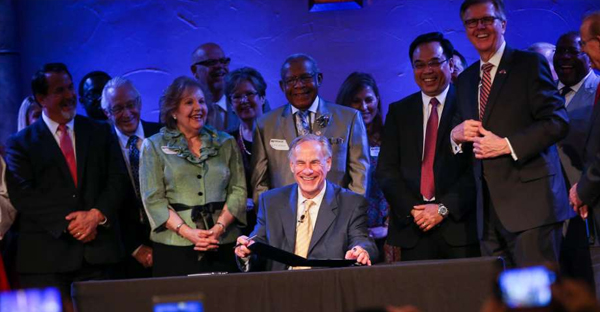 """Gov. Greg Abbott, accompanied by Lt. Gov. Dan Patrick and dozens of pastors including the """"Houston Five"""" whose sermons were subpoenaed by the city of Houston, ceremonially signs Senate Bill 24 during the service on Sunday, May 21, 2017, at Woodlands Grace Church in The Woodlands. Texas Senate Bill 24 blocks religious sermons from being subpoenaed by governmental entities. (Michael Minasi)"""