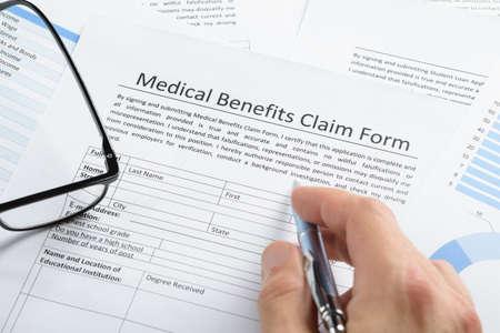 Close-up Of Hand Holding Pen Over Medical Claim Application Form - medical claim form