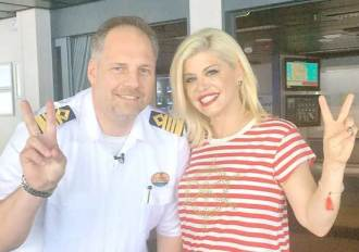 Woman takes a selfie with the river cruise captain.