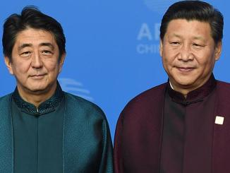 Japan's Prime Minister Shinzo Abe (left) poses with Chinese President Xi Jinping (right) upon arrival for Asia-Pacific Economic Cooperation (APEC) Summit banquet at the National Aquatics Center in Beijing on Nov 10, 2014 | Image: AFP
