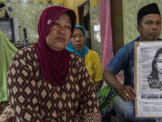 Family of beheaded Indonesian domestic worker Siti Zainab hold her portrait in East Java province on 15 April 2015 I Image: CNN