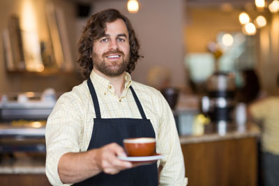 barista-holding-coffee-cup-in-cafe-l