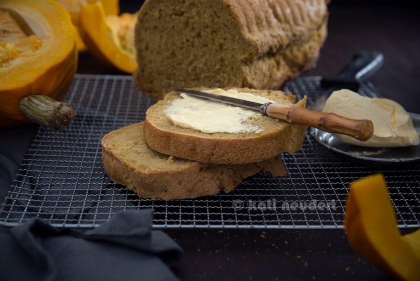 Aufgeschnittenes, selbstgebackenes Kürbisbrot mit Margarine. Vegan.