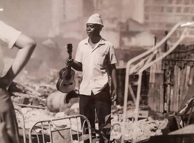 Morador resgata seu cavaquinho depois do incêndio no Morro do Pinto, até hoje investigado como criminoso. A destruição pelo fogo deixou centenas de desabrigados nos anos 1960 e possibilitou a construção do condomínio Selva de Pedra, no Leblon. Reprodução de Alexandre Gomes