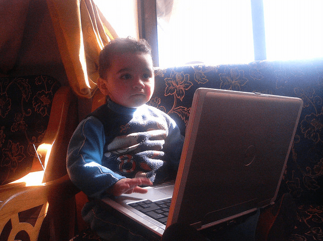 Photo of a baby working on a laptop