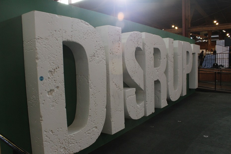 A large mural with the logo for the TechCrunch Disrupt 2011 conference stands in the center of the show floor.