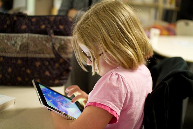 Child using an ipad, photo by Devon Christopher Adams