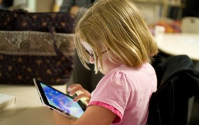 Child using an ipad, photo by Devon Christopher Adams