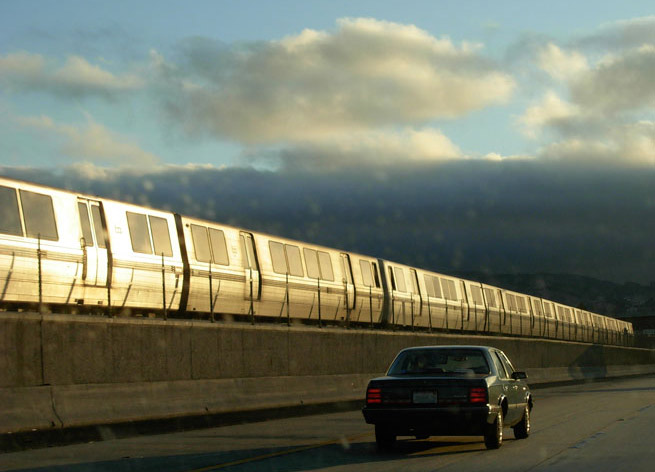 A truck drives by a BART train on the highway.