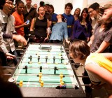 A bunch of people, who might be working at a startup, playing Foosball.