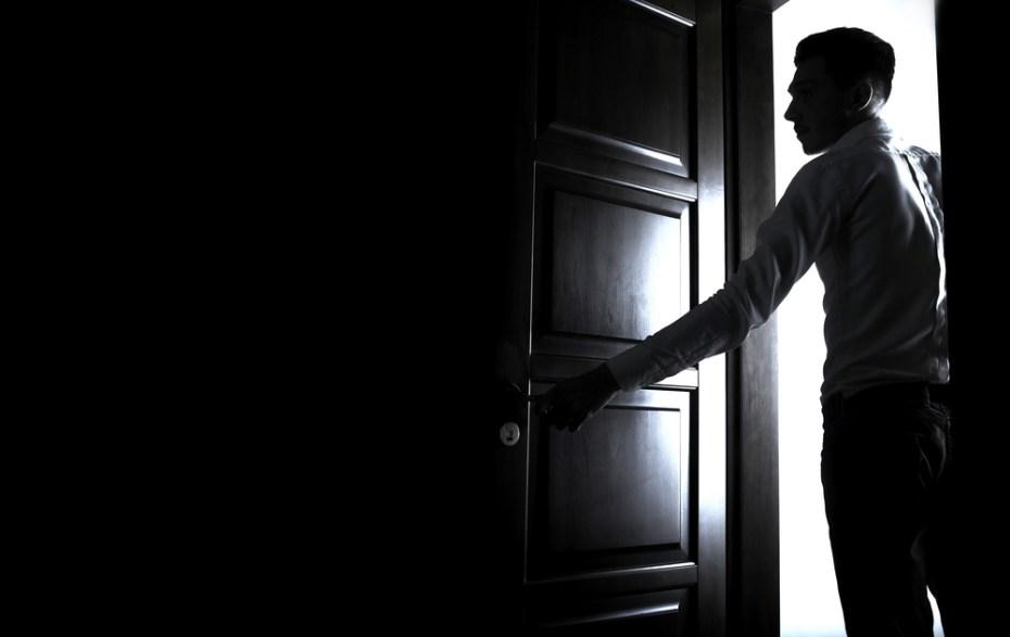 Man opens the door to dark room