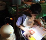 SOCCKET shining light on a student doing his homework.