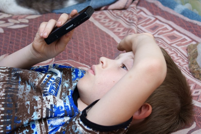 Children use smartphones to play games and browse the Internet.