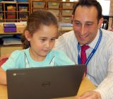 Chesterfield school district  tech chief Adam Seldow and his daughter Naomi work on a new Chromebook.