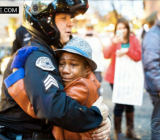 "A Portland police officer hugs a tearful 12-year-old boy, who had been holding a sign that read ""Free Hugs"" during a Ferguson demonstration."