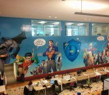 A mural at Hero City features Batman, Robin, Superman, Wonder Woman -- and Tim Draper.