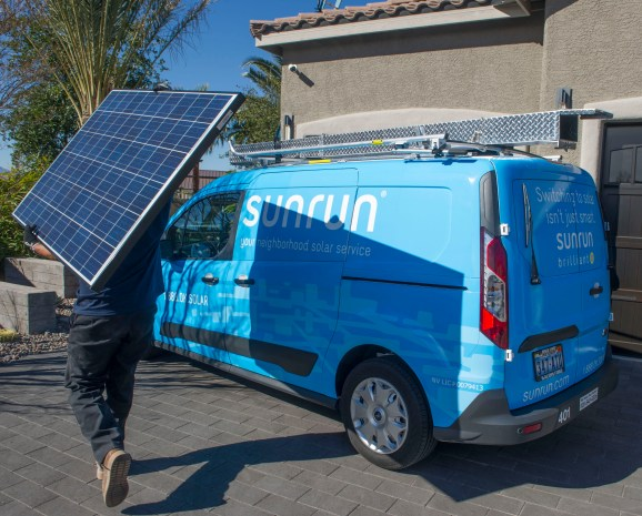 A Sunrun employee installs a solar panel on the roof of a house.