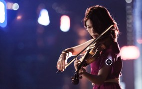 A violinist plays to the beat set by the Pulse wearable device, which she's wearing on her arm.