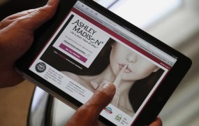 Ashley Madison founder Noel Biderman demonstrates his website on a tablet computer during an interview in Hong Kong on August 28, 2013.