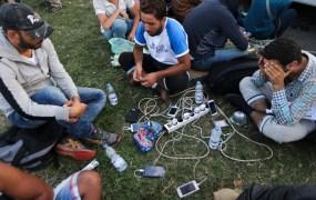 Migrants charge their mobile phones at the Croatia-Slovenia border crossing at Bregana, Croatia, September 19, 2015.