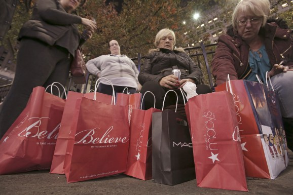 Women sit outside after shopping at Macy's Herald Square store during the early opening of the Black Friday sales in the Manhattan borough of New York