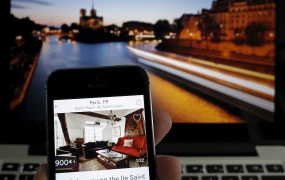 An illustration picture shows the Paris apartment offer by American actress Judith Freiha on the Airbnb web page displayed on a smatphone in front of a general view of the Ile Saint-Louis on the Seine river in Paris, France, August 9, 2015. Nowhere in the world has more accommodation available on Airbnb than Paris. Now the home-sharing website that has transformed budget travel to the French capital is giving its super-deluxe hotels a fright too.