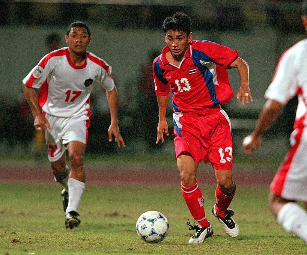 11 Nov 2000: Kiatisuk Senamuang of Thailand takes on the defense during the Tiger Cup match between Indonesia and Thailand at Rajamangala Stadium in Bangkok, Thailand. Thailand defeated Indonesia 4-1. Mandatory Credit: Stanley Chou/ALLSPORT