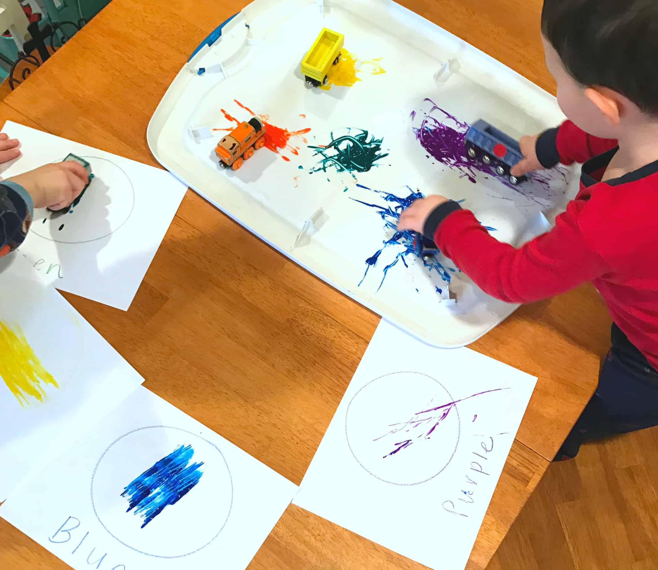 Painting with trains is a really great way to create a hands-on experience while learning colors! This fun method combines art with learning for toddlers.