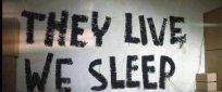 "On a wall inside the church is written ""They Live We Sleep"", a phrase that describes the fundamental different between the elite and the masses. Those in power have access to the means and the knowledge to live a full life while the rest of the population is sedated, dumbed-down and manipulated into a zombie-like status in order for it to be as easily manageable as possible by the masters."