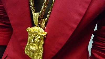 "Kanye wearing a Jesus piece chain, a staple in hip-hop fashion. By displaying a melted down Jesus face on the album cover while naming the album ""Yeezus"", Kanye conveyed the fact that the symbol of Jesus is not an untouchable symbol of divinty and that he can also reach that status."