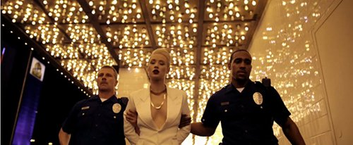 "In a scene playing in parallel to the one above, Iggy is shown dressed in white and being arrested by the police. While this might be her being arrested for setting her boss' car on fire, the scene is shown at the same time as the one above and not after it. The scene can represent what happens after initiation in the industry: the ""good girl"" dresssed in white is taken away while the Illuminati-girl dressed in black (with an All-Seeing eye) stays."