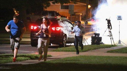 TV crew fleeing after receiving tear gas near its equipment.