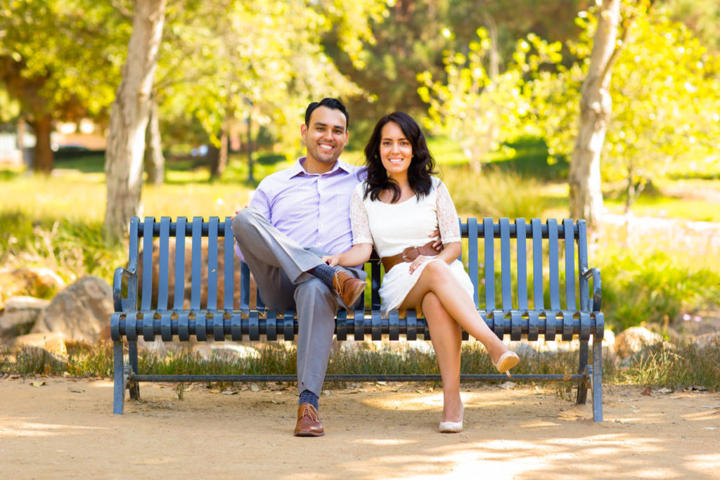 Engaged couple sitting on park bench smiling before their Laguna Beach engagement session