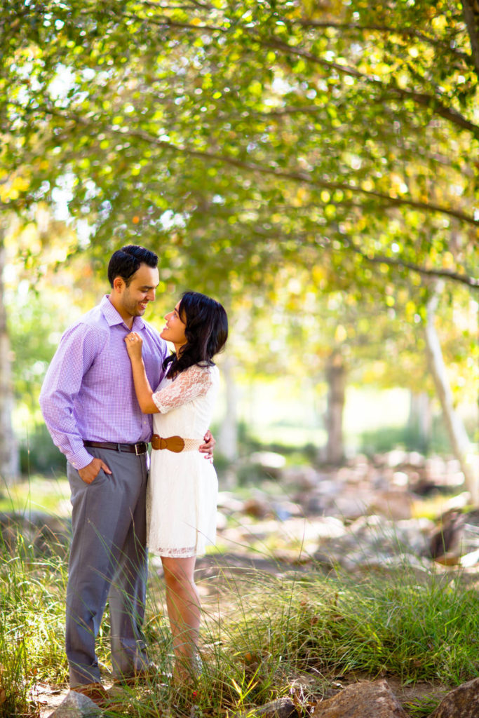 Couple standing under a canopy of trees in Irvine before their Laguna Beach engagement session