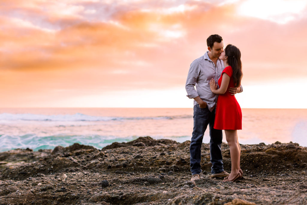 Couple looking at each other lovingly with an epic sunset behind them at their Laguna Beach engagement session