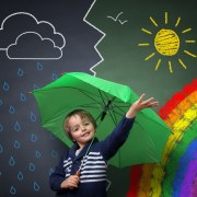 Child holding an umbrella standing in front of a chalk drawing of changing weather from rain storm to sun shine with a rainbow on a school blackboard